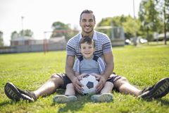 Man with child playing football on field Royalty Free Stock Images
