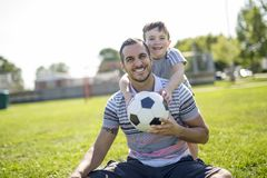 Man with child playing football on field Stock Images