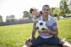 Man with child playing football on field Stock Image