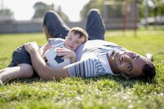 Man with child playing football on field Royalty Free Stock Photos