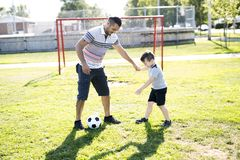Man with child playing football on field Stock Photos