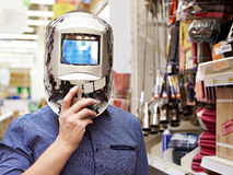 Men choose protective mask welder in store construction and tool Stock Photos