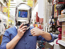 Men choose protective mask welder in store construction and tool. Men choose a protective mask Welder store construction materials and tools Royalty Free Stock Images