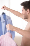 Men choosing shirt to wear. Cheerful young men with naked torso Royalty Free Stock Photo