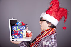 Men in christmas cap with gift boxes and notebook. Stock Photo