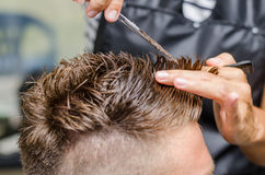 Men& x27 ; ciseaux de coupe de cheveux de s dans un salon de beauté Images stock