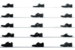 Men classic shoes displayed on shop shelves. Against back lit white background. High contrast black and white abstract looking picture Royalty Free Stock Photography