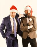 Men in classic suits and Santa hats isolated on white. Background. Business and Christmas vacation concept. Colleagues with beards rely on each other royalty free stock image