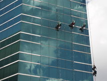 Men cleaning glass building by rope access at height Stock Photo