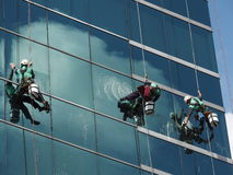 men cleaning glass building by rope access at height stock images