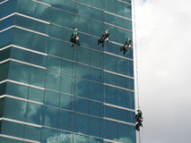 Men cleaning glass building by rope access at height stock photography