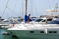 Men cleaning a yacht, Sotogrande. Men cleaning a yacht in the marina, Puerto Sotogrande, Cadiz Province, Andalucia, Spain, Western Europe Stock Image