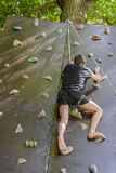 Men climbing on a wall. Young man climbing on a wall in an outdoor climbing center Stock Photo