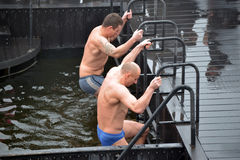 Men climbs out of the icy water Royalty Free Stock Photography