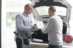Men with clipboard and pen standing near car royalty free stock images