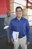 Men With Clipboards In Front Of Stacks Of Wood Stock Photography