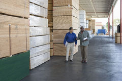 Men With Clipboards Walking Along Stacks Of Wood Stock Photography