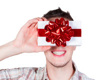 Men closes his eyes by gift box. Smiling man in Santa hat closes his eyes by gift box Royalty Free Stock Images