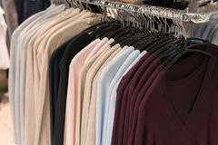 Men clothes, row of sweatshirts, shopping. Men clothes, row of sweatshirts on the hanger in the shop, shopping. Wardrobe of male clothing on the racks Stock Image