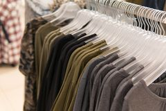 Men clothes, row of t-shirt collection, shopping. Men clothes, row of t-shirt collection on the hanger in the shop, shopping. Wardrobe of male clothing on the Stock Photo