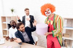 A man in a clown suit is holding a box with a surprise in his hand. royalty free stock photography