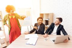 A man in a clown suit stands beside men in business suits, who sit at the desk. Royalty Free Stock Photo