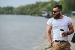 Men and coffee on the beach. Man with a cup of coffee looking at the beach royalty free stock photo