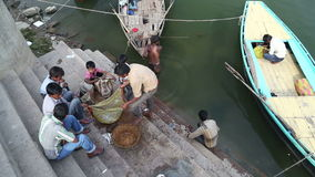 Men collecting fish in net at ghat in Varanasi, with children sitting aside. stock footage