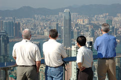 Men and the commerical city. Four gentlemen looking at the commerical city of Hong Kong royalty free stock photo