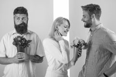 Men competitors with bouquets flowers try conquer girl. Broken heart concept. Girl smiling made her choice. Girl popular. Receive lot male attention. Woman royalty free stock photography
