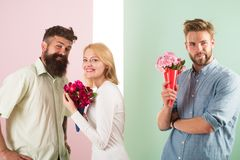 Men competitors with bouquets flowers try conquer girl. Broken heart concept. Girl smiling made her choice. Woman happy. Takes bouquet flowers romantic gift stock photography