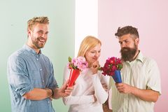 Men competitors with bouquets flowers try conquer girl. Girl likes to be in middle attention. Love triangle. Woman. Thoughtful has opportunity choose partner stock photo