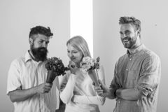Men competitors with bouquets flowers try conquer girl. Girl likes to be in middle attention. Love triangle. Woman royalty free stock photography