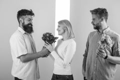 Men competitors with bouquets flowers try conquer girl. Girl smiling made her choice. Broken heart concept. Woman happy. Takes bouquet flowers romantic gift stock image