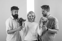 Men competitors with bouquets flowers try conquer girl. Girl smiling reject gifts. Feminism concept. Woman smiling. Reject both male partners. Out of relations royalty free stock images