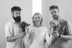 Men competitors with bouquets flowers try conquer girl. Girl smiling reject gifts. Out of relations. Feminism concept. Woman smiling reject both male partners stock images