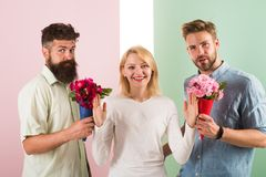Men competitors with bouquets flowers try conquer girl. Girl smiling reject gifts. Out of relations. Feminism concept. Woman smiling reject both male partners stock photo