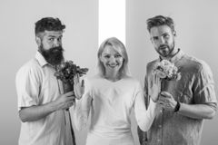 Men competitors with bouquets flowers try conquer girl. Girl smiling reject gifts. Out of relations. Girl popular. Receive lot men attention. Feminism concept royalty free stock photo