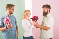 Men competitors with bouquets flowers try conquer girl. Girl smiling made her choice. Broken heart concept. Woman happy. Takes bouquet flowers romantic gift stock photos