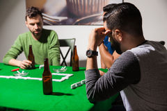 Men concentrated on a dominoes game. Male friends drinking beer and trying to concentrate on a dominoes game at home Royalty Free Stock Image
