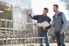 Men on construction site holding paperwork Stock Photo