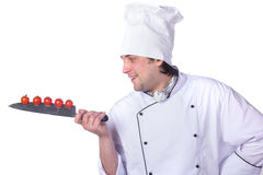 Men cook. cherry tomatoes cut into the knife Royalty Free Stock Images