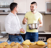 Men cooking potato soup Stock Photos
