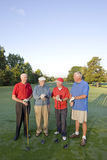 Men on Course with Clubs. Four elderly men are standing together on a golf course. They are holding their clubs, smiling, and looking at each other and away from Royalty Free Stock Photography