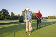 Men on Course with Clubs. Two elderly men are standing together on a golf course. They are holding their clubs, and one is about to hit the ball.  Horizontally Royalty Free Stock Photos