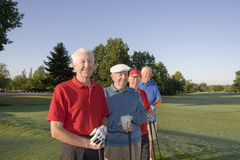 Men on Course with Clubs. Four elderly men are standing together on a golf course. They are holding their clubs, smiling, and looking at the camera Royalty Free Stock Images