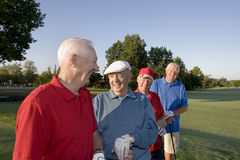 Men on Course with Clubs. Four elderly men are standing together on a golf course. They are holding their clubs, smiling, and looking at each other Royalty Free Stock Image