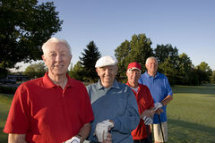 Men on Course with Clubs. Four elderly men are standing together on a golf course. They are holding their clubs, smiling, and looking at the camera. Horizontally stock photography