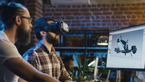 Men coworking on graphics of video game. Two men using VR technologies and computer to create video game and developing graphics for movie stock video footage