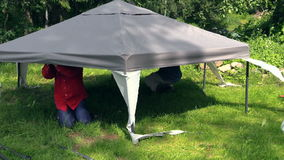 Men crawled under gazebo canvas top fix on metal structure stock video footage